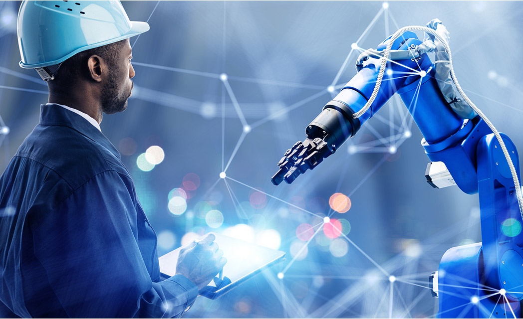 Image of a man looking at and working with a robotic arm.